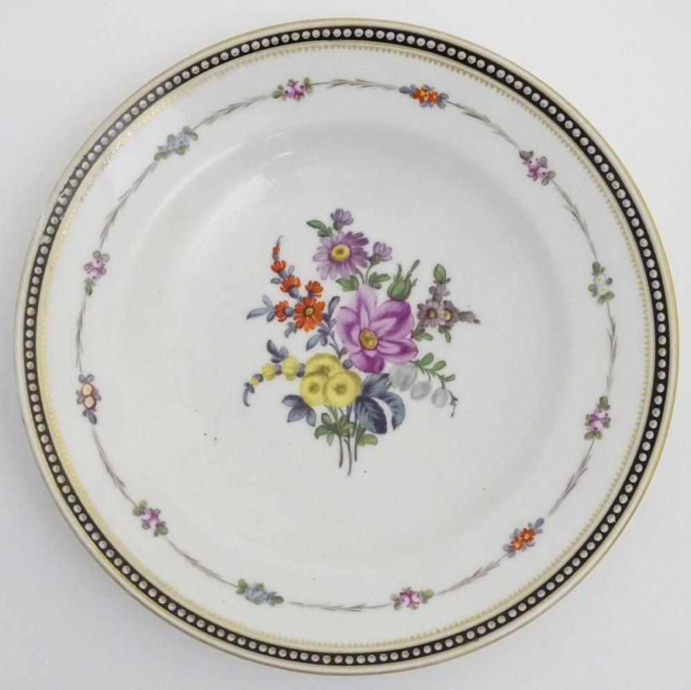 A Continental plate decorated with a central arrangement of flowers, a floral border and a banded ri