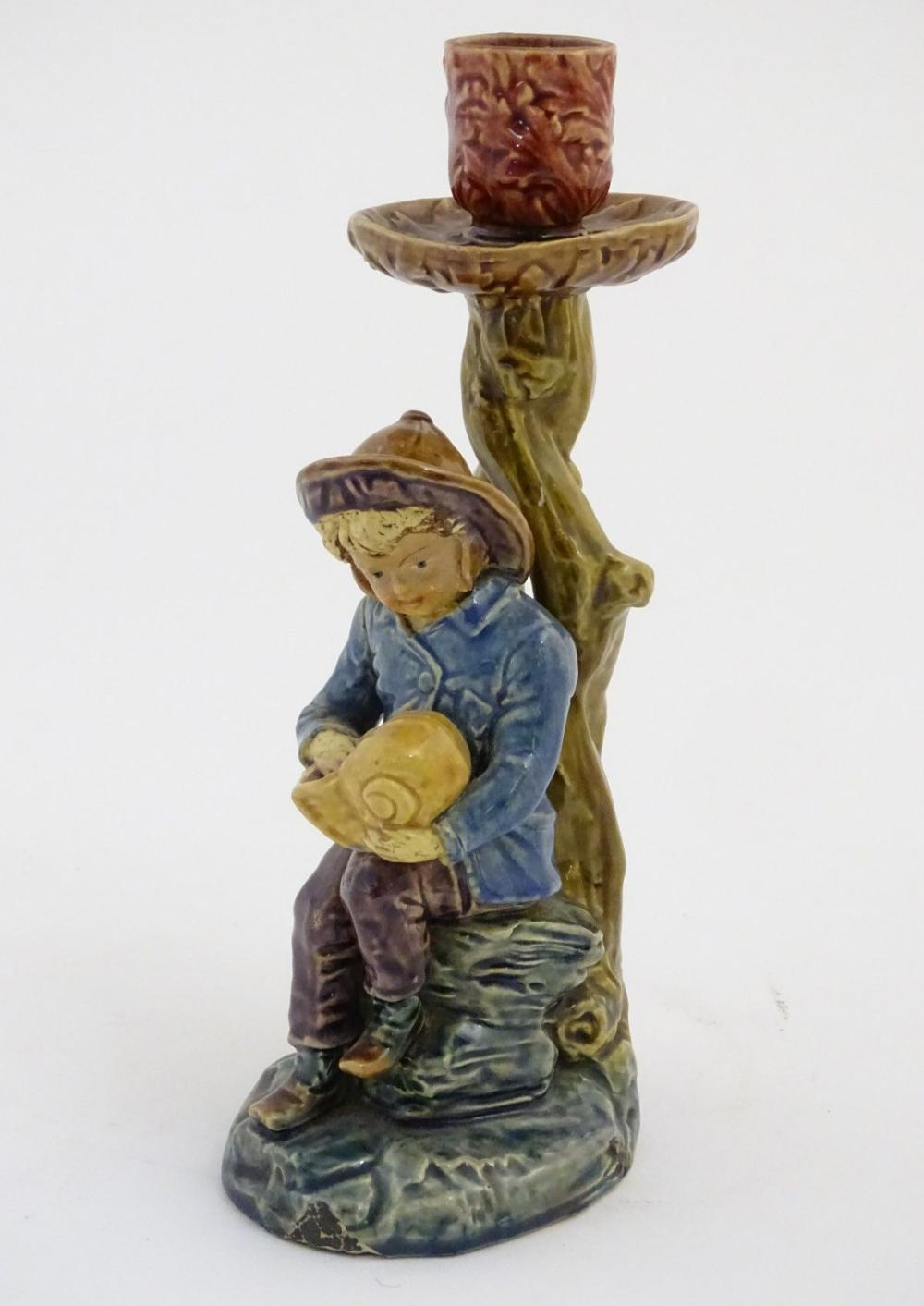 A continental candlestick decorated with a fisherman boy holding a nautilus shell. Stamped under 'BD