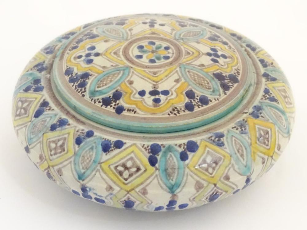 An Islamic circular lidded pot decorated with banded hand painted shapes. Character marks under. App