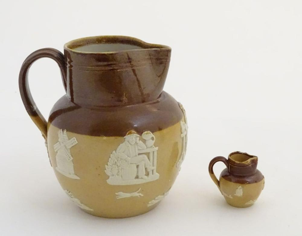Two Royal Doulton two-tone salt glazed jugs. Decorated in relief with hunting scenes, windmills, dog