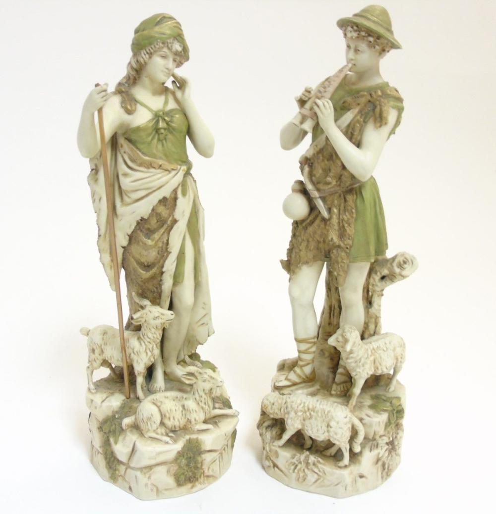 A pair of early 20thC Royal Dux Bohemia figures comprising a shepherd playing the flute and a shephe