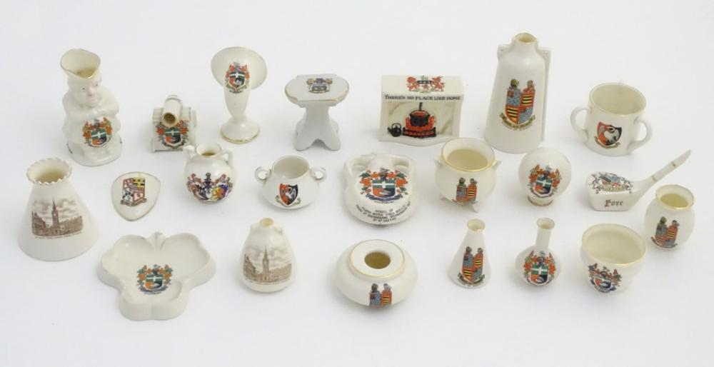 A quantity of local interest crested ware of various forms, including a miniature Toby jug, cups, ju