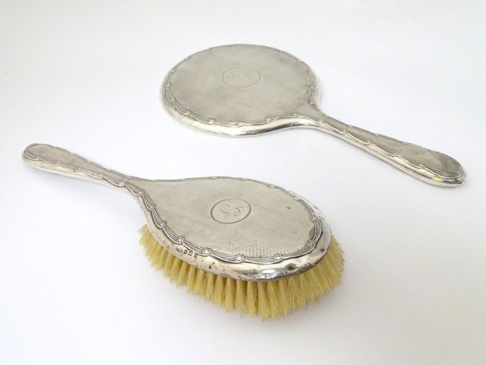 A silver backed hand mirror and brush with engine turned decoration. Hallmarked Birmingham 1911/12