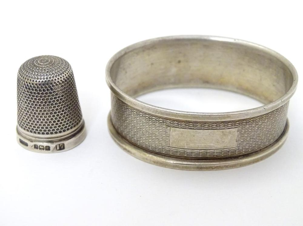 A silver napkin ring Birmingham 1951 maker B & Co. Together with a thimble hallmarked Birmingham 192