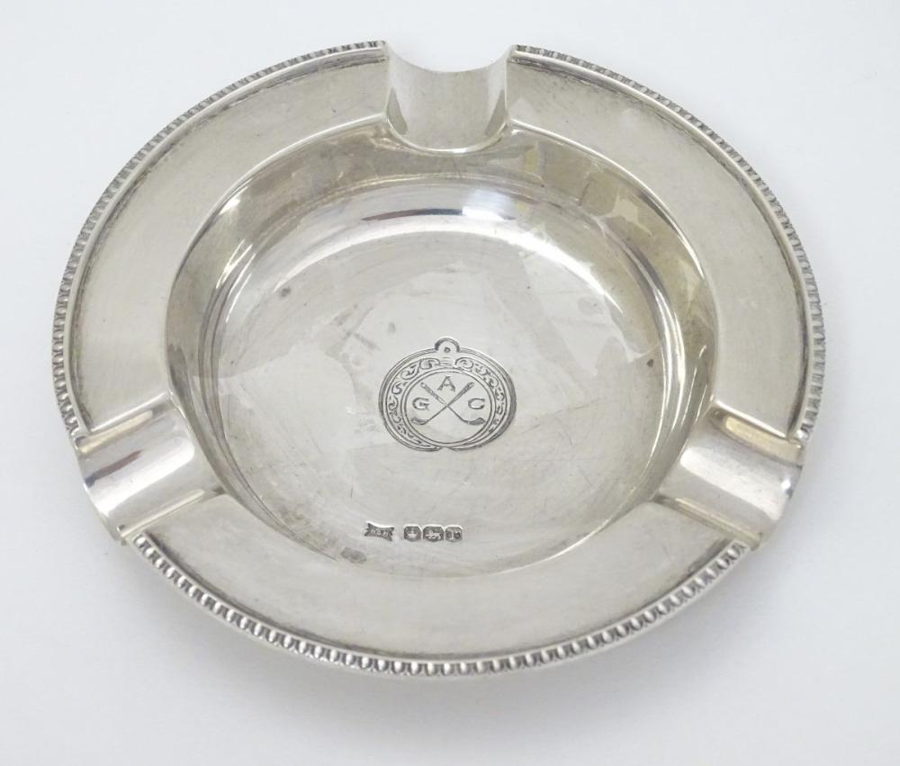 A silver ash tray with engraved crossed golf club emblem titled AGC. Hallmarked Sheffield 1934 maker