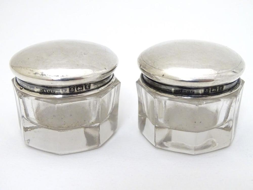 A pair of glass pots with silver tops hallmarked Birmingham 1918 maker G & C Ltd. 1 1/4'' wide