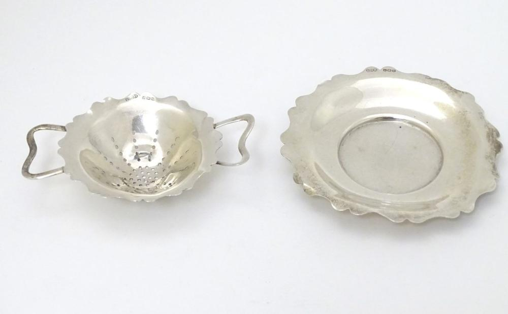 A silver tea strainer and stand hallmarked Sheffield 1920 maker E J Houlston. 4 1/4'' wide (74g) (2)