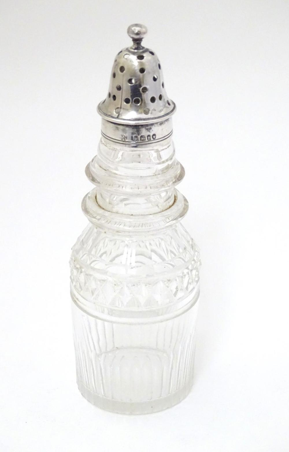 A cut glass pepperette with silver top hallmarked London 1864 maker George John Richards & Edward Ch