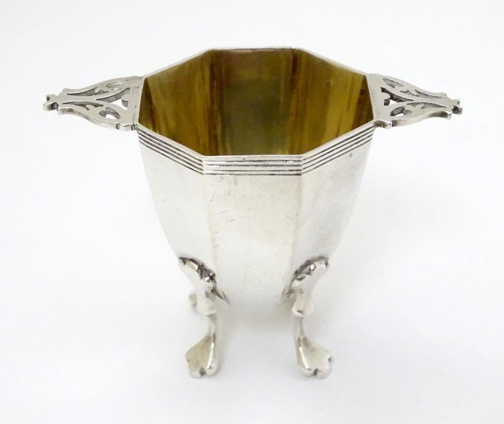 A silver octagonal formed salt / pepper base with twin handles and gilded interior. Hallmarked Londo