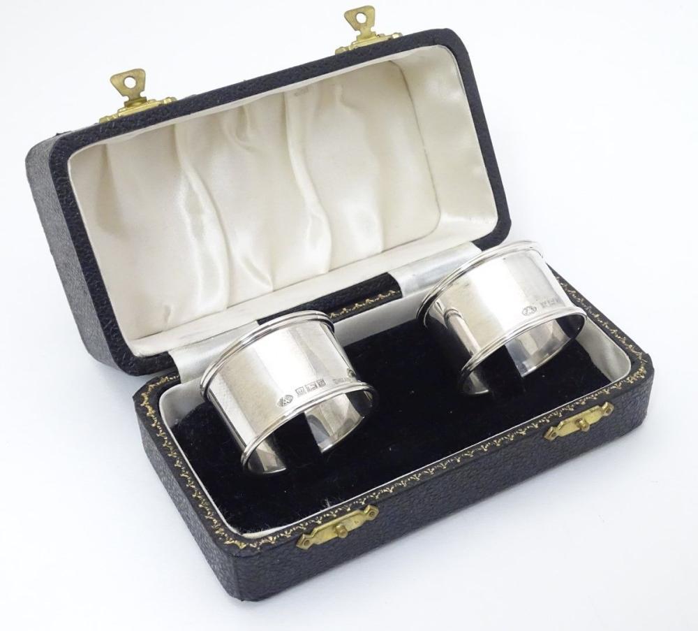 A cased pair of silver napkin rings hallmarked Birmingham 1954/1956 maker Adie Bros Ltd.
