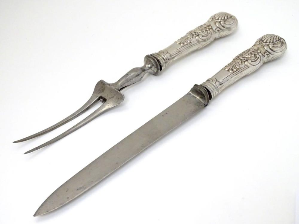Carving knife and fork with white metal Queens pattern handles. The knife 12 1/2'' long