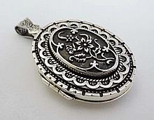 A large silver locket of oval form with floral decoration. Approx 2'' long