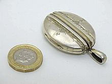 A white metal locket of oval form approx 2'' long