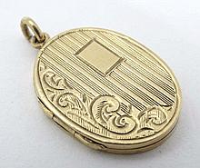 A 9ct gold locket of oval form hanging engraved acanthus and engine turned