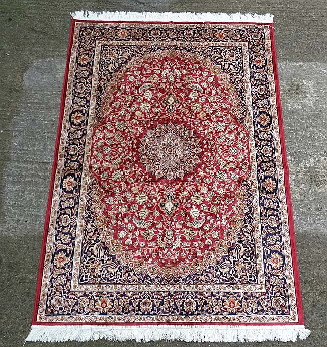 Carpet / Rug : A Machine made woollen carpet , with red central ground, mid