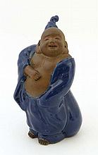 A Bizan Hotei figure, biscuit finish to body and