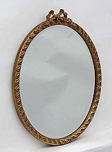 A  mid - late 20thC oval wall mirror with bevelled glass and gilt surround