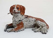 A 21stC cold painted bronze inkwell depicting a recumbent dog holding a fea
