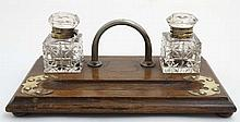 A late 19thC inkstand / Standish having 2 glass inkwells with hinged lids.,