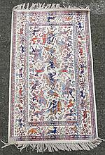 Carpet / rug : a silk small rug with images of figures on horseback, antelope, lions and tigers in buff ground with blues, reds, mustards etc. 49'' long x 27'' wide.