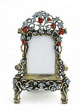 A cast photo frame formed as a an old wooden chair with fruiting vine decoration with green enamel and red stone decoration. 21stC. 8'' high overall