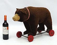An early / mid 20thC '' Steiff '' straw filled pull-along plush bear with growler having amber coloured plastic eyes and red collar on an iron frame with red painted wooden wheels, bears Steiff button to left ear. 16'' high