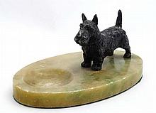 An Art Deco cast spelter model of a West Highland terrier dog with black decoration mounted upon an oval alabaster base with dished recess to front. the whole 7'' 3 1/2'' x 4 1/2''
