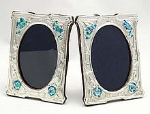 A pair of silver photograph frames with enamel floral decoration in the Art Nouveau style. Maker RH. 21stC. Each 6'' x 5 3/4'' overall