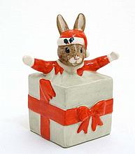 A Royal Doulton Bunnykins figure formed as a rabbit emerging from a Christmas present. entitled ' Christmas Surprise ' 3 1/2'' high