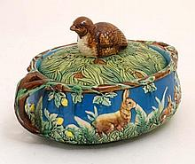 A 20thC George Jones style Majolica twin handled lidded game tureen , marked 1679, decorated to side with hares and leverets amongst foliage , the top knop formed as a quail, in shades of green, brown and blue, the handles formed as branches. 8''