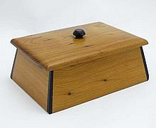 A cedar wood jewellery box with ebony inlay and hinged lid opening to reveal a mirror within. 6 1/2'' wide x 4 3/4'' x 3''