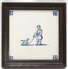 A 19thC Delft tile decorated with image of a young boy with pull along toy horse. Framed. The whole 7 1/4'' sq.