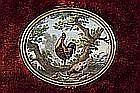 Miniature ovale en émail polychrome représentant un coq perché sur un arbre observant une poule et ses poussins picorant.