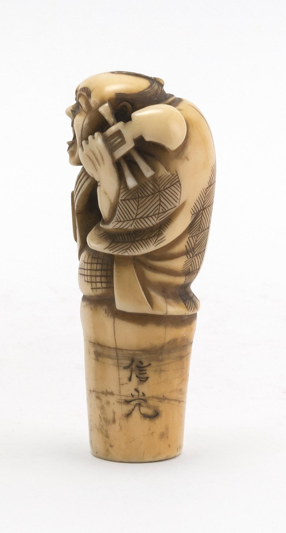 JAPANESE CARVED IVORY CANE HANDLE In the form of a musician playing a biwa. Signed. Length 3