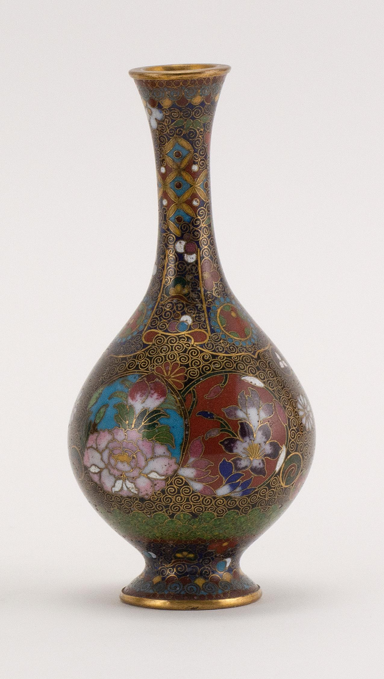 """JAPANESE MINIATURE CLOISONNÉ ENAMEL VASE In bottle form, with an extensive floral design on a black and gilt ground. Height 5""""."""