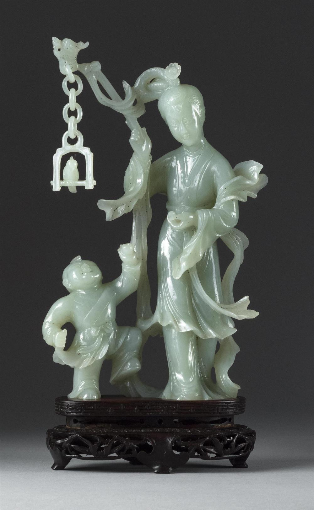 """CHINESE CELADON JADE FIGURE GROUP A mother and child standing under a bird perched on a swing. Height 7.25"""". With wood stand and fit..."""