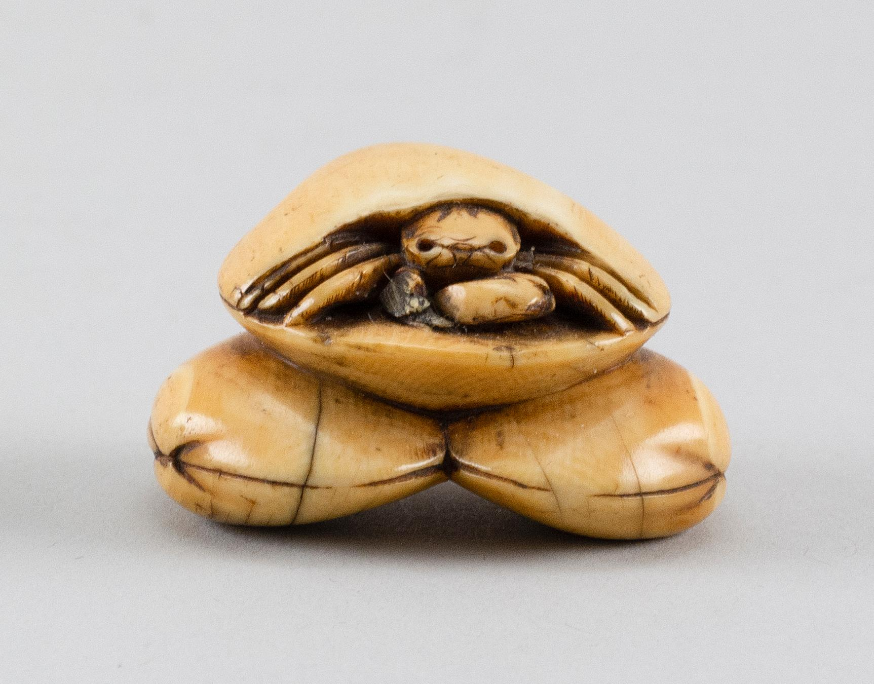 """IVORY NETSUKE In the form of a crab crawling out of a clamshell mountain. Height 1.8""""."""