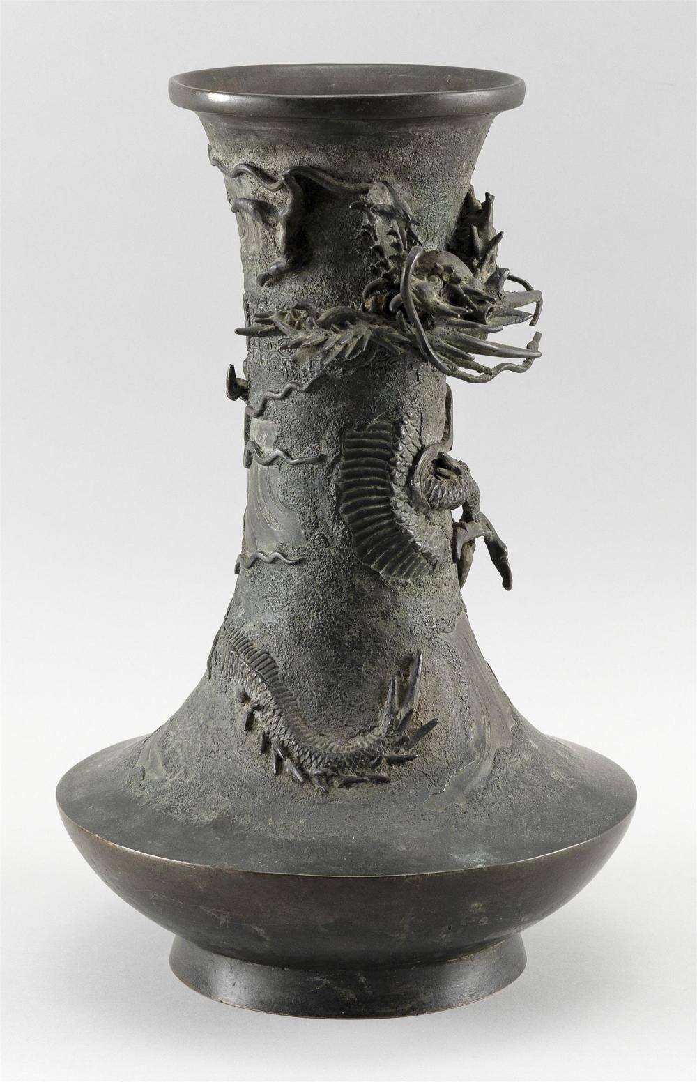 JAPANESE BRONZE VASE In squat baluster form, with a raised dragon entwined around the neck and an incised wave, brocade and mon desi...