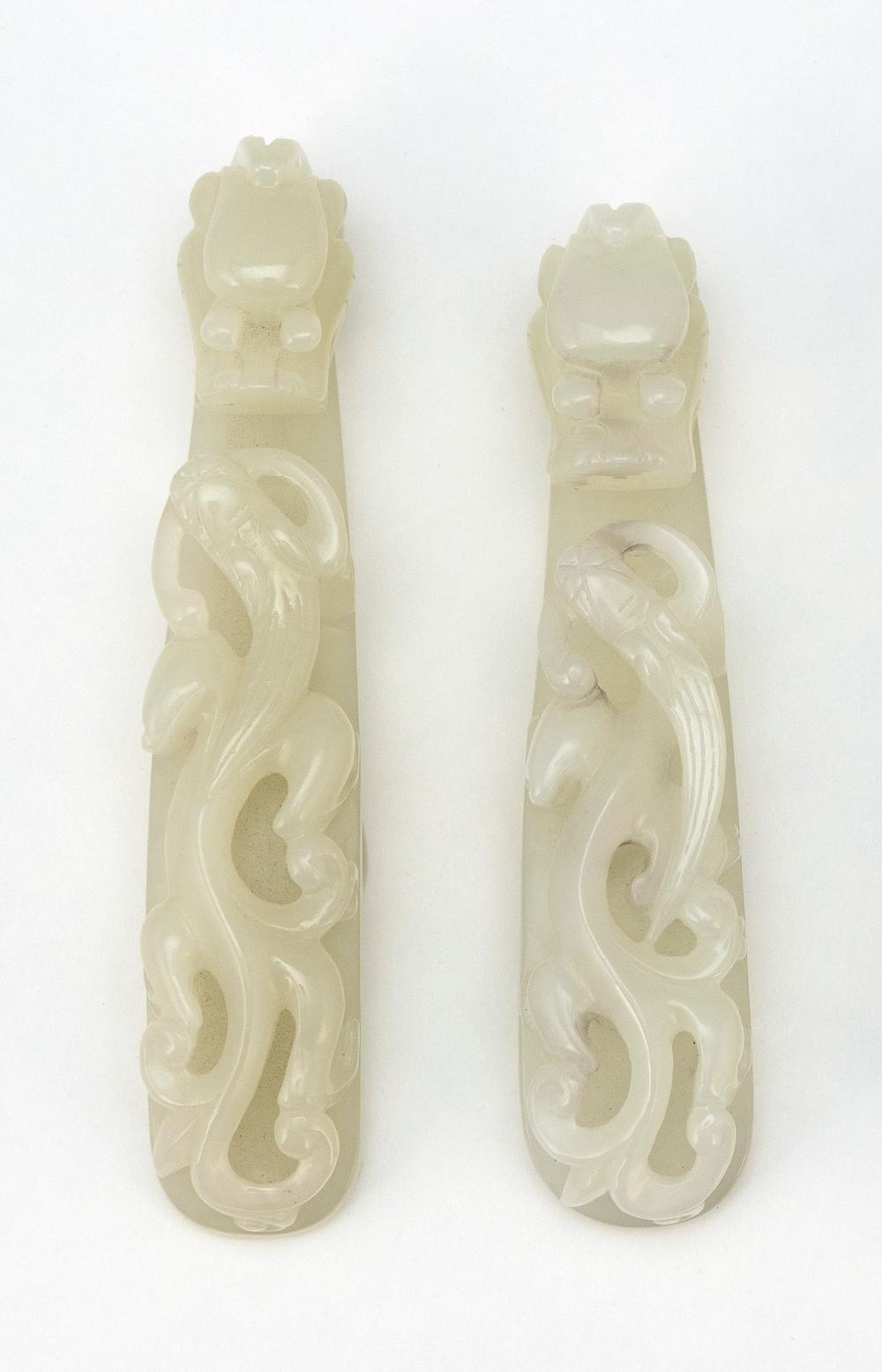 TWO CHINESE PALE CELADON JADE GIRDLE HOOKS Both carved with raised qilong dragons along the shafts and dragon's-head-form hooks. Len..