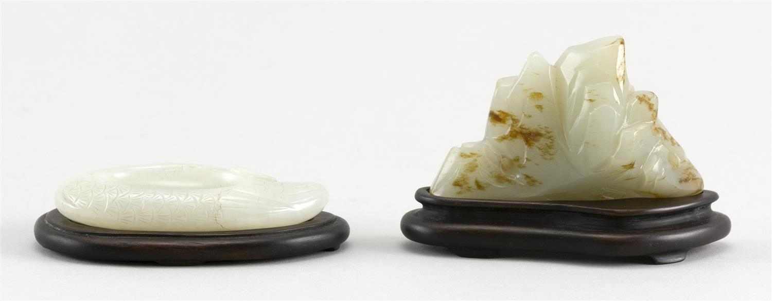 "TWO CHINESE CARVED PALE CELADON JADE PIECES A mountain range with some russet skin tones, height 2"" and length 7"", and a water dropp..."