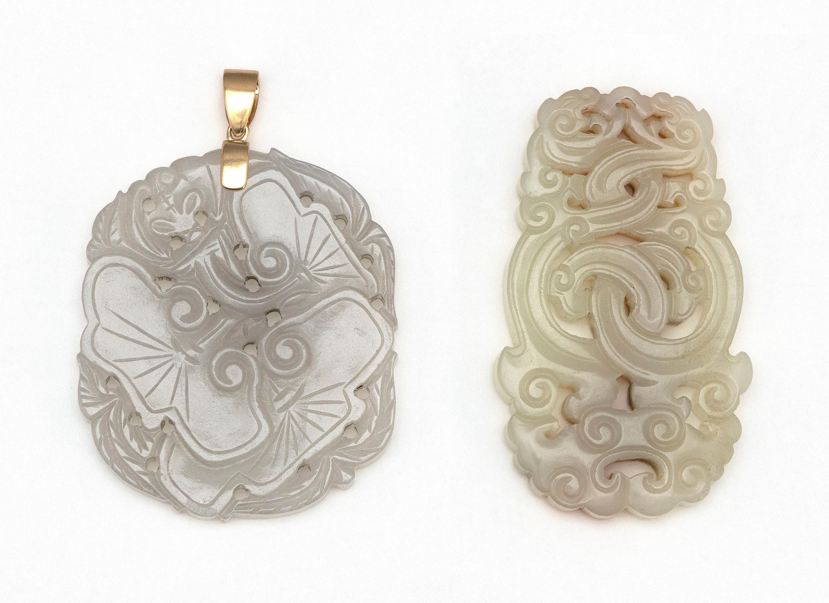 """TWO CHINESE CARVED WHITE JADE PENDANTS 1) Openwork-carved in the form of entwined ruyi. Some russet skin tones. Length 2.5"""". 2) In t..."""