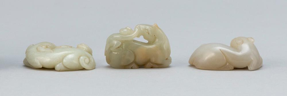 THREE CHINESE CARVED PALE CELADON JADE ANIMAL FIGURES A recumbent horse with a monkey on its back, a recumbent cat, and a recumbent...