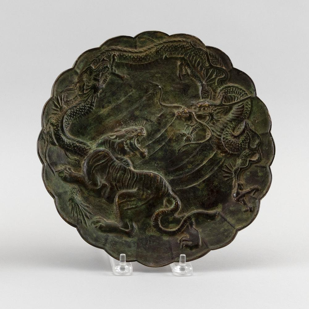 JAPANESE PATINATED BRONZE PLATE With scalloped edge and elaborate decoration of a raised dragon and tiger. Calligraphic inscription...