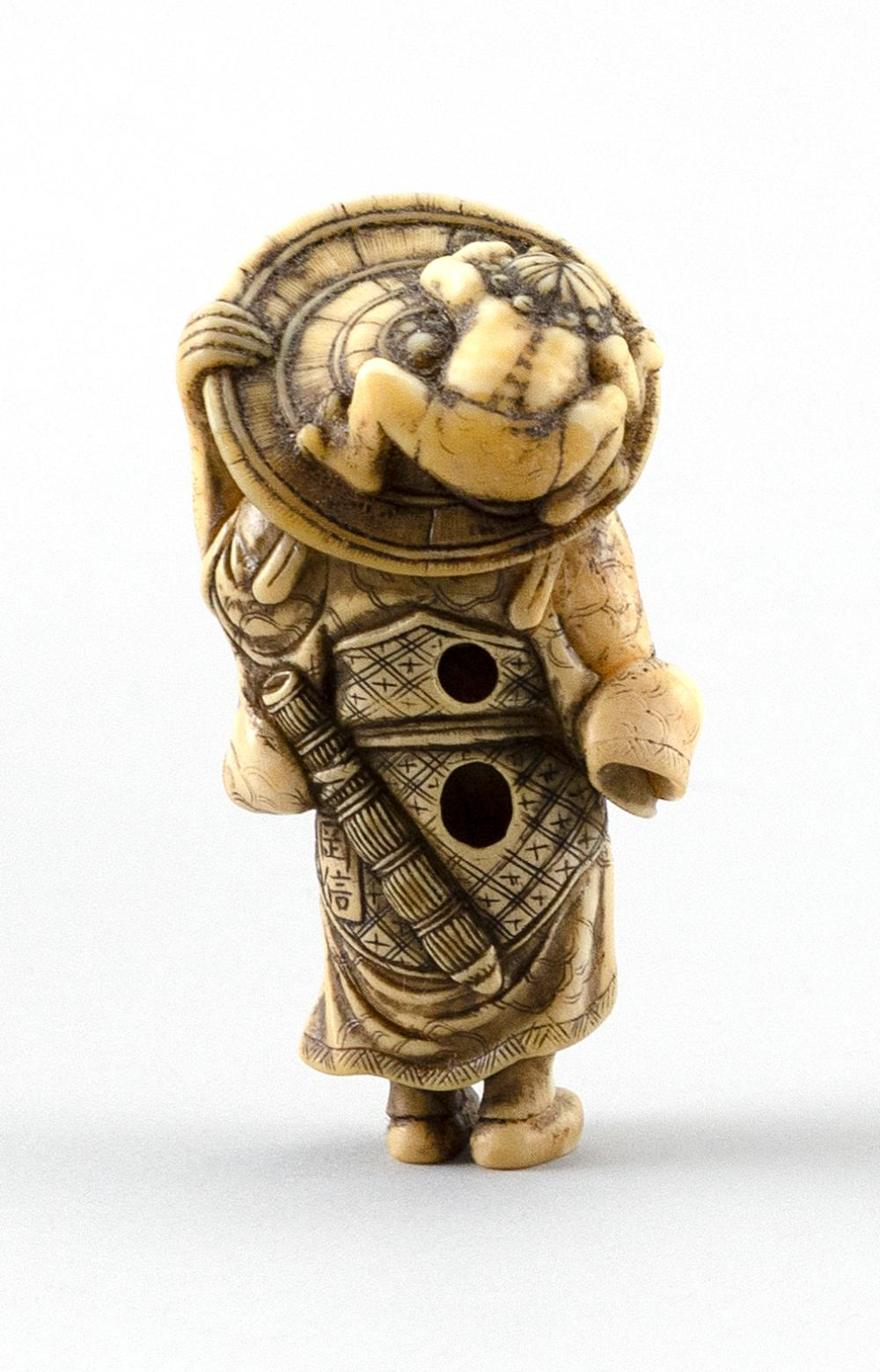 IVORY NETSUKE Signed Okanobu. In the form of a man holding his sword in one hand and his sedge hat, on which an oni is riding, in th...