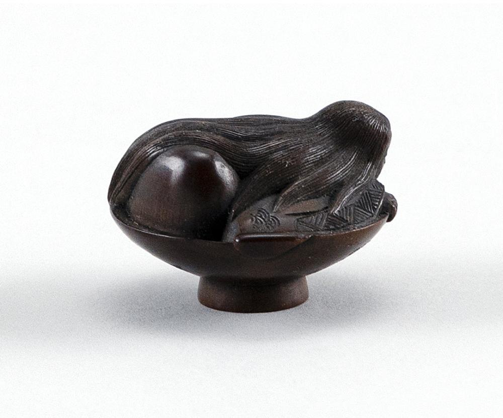 WOOD NETSUKE In the form of a witch covering the expanse of a sake cup. Signed on base. Height 1