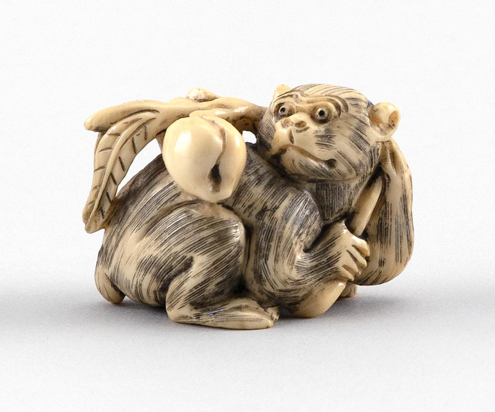 """IVORY NETSUKE In the form of a monkey holding a peach branch. Signed on base. Length 2""""."""