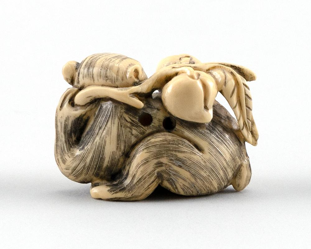 IVORY NETSUKE In the form of a monkey holding a peach branch. Signed on base. Length 2