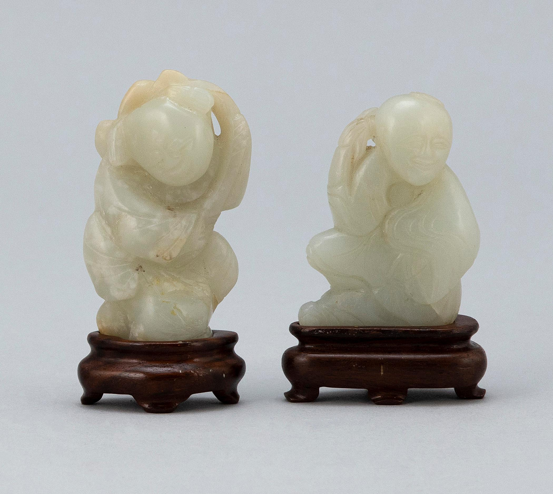 "TWO CHINESE WHITE JADE CARVED FIGURES A farmer and a scholar, heights 2.5"" and 2"". Mounted on wood stands. Purchased at Gump's, San..."