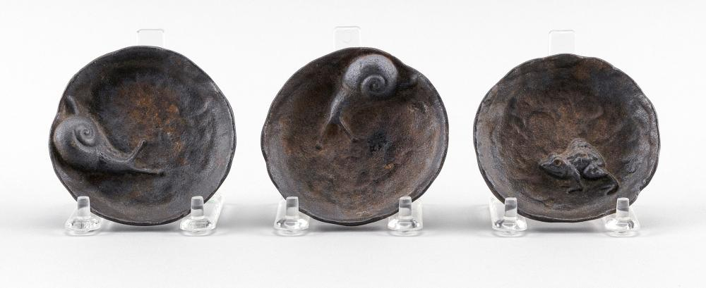 """THREE JAPANESE CAST IRON DISHES Two inset with a snail, and one with a frog, each with traces of gilding. Lengths approx. 3"""". Proven..."""