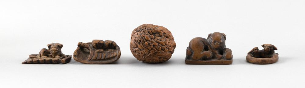 "FIVE WOOD NETSUKE AND OKIMONO 1) Carved nut-form okimono with figures and a tiger. Length 2"". 2-3) Two puppy-form netsuke. Lengths 1..."